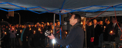 Matt Fulton plays and sing's 'Imagine' by John Lennon to a backdrop of residents holding candles.
